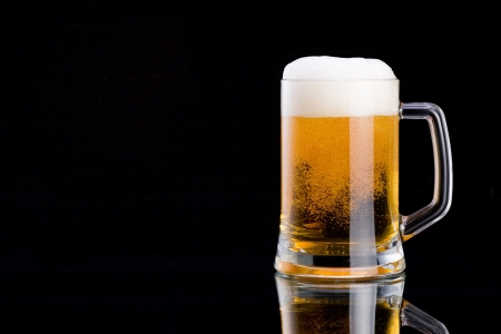 overflow: Mug fresh beer with cap of foam on a black background Stock Photo