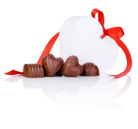 Chocolate candies and White gift in the form of heart with a bow of red ribbon Isolated on white background photo