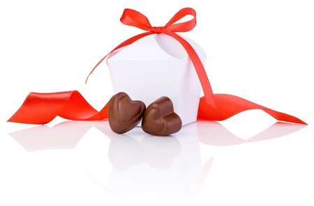 sweet heart: Two chocolate candies in heart shape, white box and red ribbon Isolated on white background
