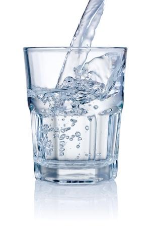 白い背景で隔離のグラスに水を入れる 写真素材