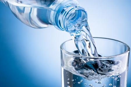 tomando agua: Verter el agua de la botella en un vaso sobre fondo azul Foto de archivo