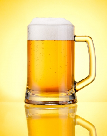 Mug fresh beer with cap of foam isolated over yellow background photo