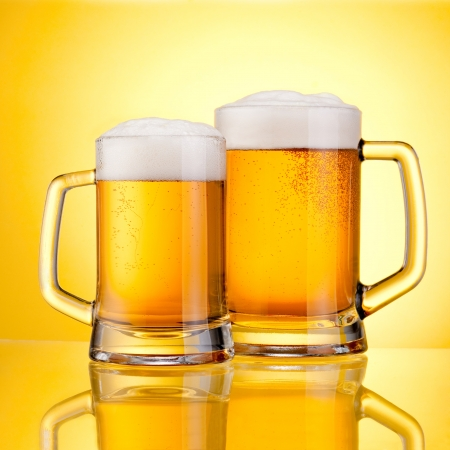 Two Mugs of fresh beer with cap of foam, isolated on yellow background Stock Photo - 22161866