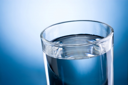 potable: Close-up glass of water on a blue background