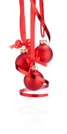 Three Red Christmas ball hanging with ribbon bow and curling paper Isolated on white background