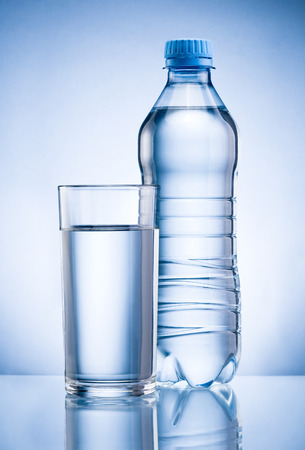 Plastic bottle and glass of drinking water isolated on blue background Banco de Imagens