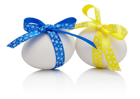 Two Easter eggs with festive blue and yellow bow isolated on white background photo