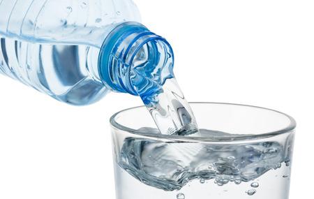白い背景で隔離のプラスチック ボトルからの水のガラスを注ぐ