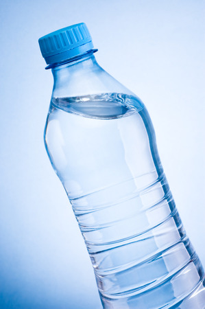 slant: Close-up plastic bottle of drinking water obliquely on a blue background