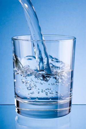 purified water: Verter agua en un vaso sobre un fondo azul