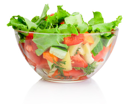 Fresh vegetable salad in transparent bowl isolated on white Фото со стока