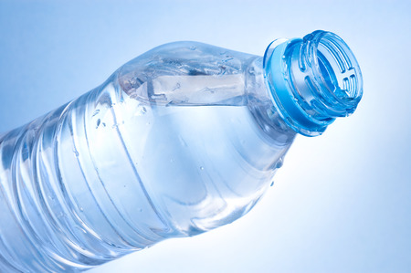 agua purificada: Abrir una botella de agua sobre fondo azul Foto de archivo