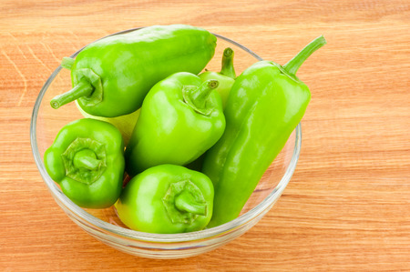 bell peper: Green peppers in transparent glass bowl on wooden board Stock Photo