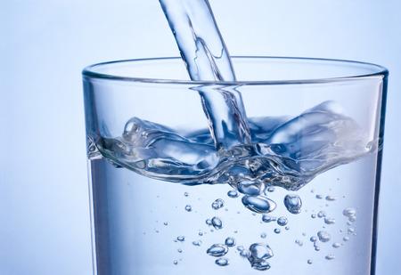 青色の背景にガラスに水を注いでクローズ アップ 写真素材