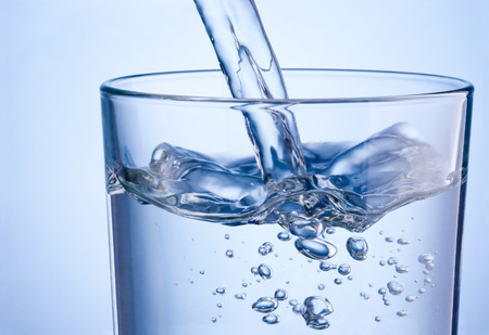Close-up pouring water into glass on a blue background