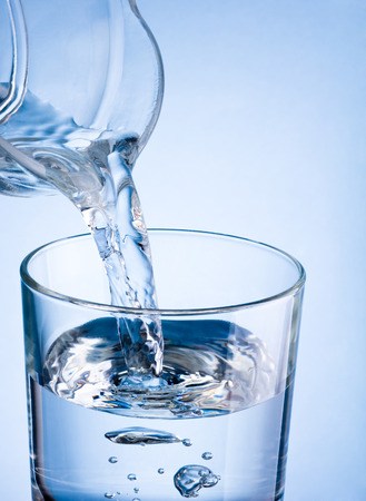 Close-up pouring water from a jug into glass on a blue background