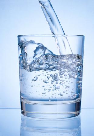 vaso de agua: Verter agua en vidrio en el fondo azul