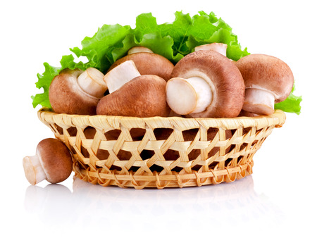 basketful: Fresh field mushroom in basket and Leaves of green salad Isolated on white background Stock Photo
