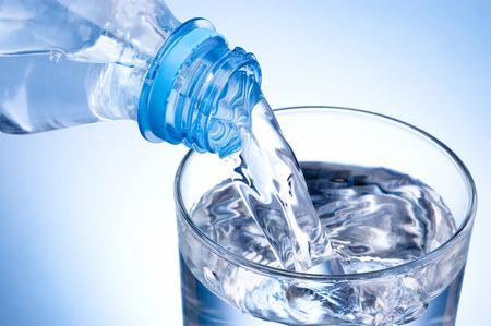 Primer plano Echar vaso de agua de una botella de plástico sobre fondo azul