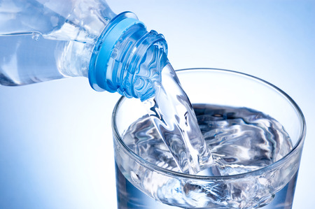 agua: Primer plano Echar vaso de agua de una botella de plástico sobre fondo azul