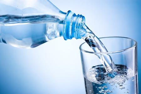 purified water: Primer plano vertiendo el agua de botella en el vidrio sobre fondo azul