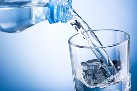 Close-up pouring water from bottle into glass on a blue background