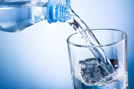 gaseosas: Primer plano vertiendo el agua de la botella en el vidrio en un fondo azul