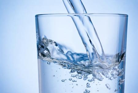 Close-up van het gieten van water in glas op blauwe achtergrond