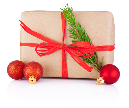 tied in: Christmas gift in kraft paper tied a red braid, pine tree branch and bauble Isolated on white background