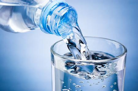 Verser de l'eau de la bouteille en verre sur fond bleu