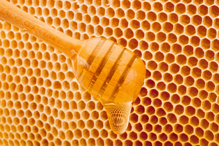 Honey dripping from dipper on background honeycomb