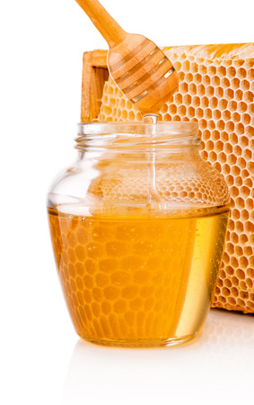 Honey dripping from dipper into glass jar on background honeycomb Banco de Imagens