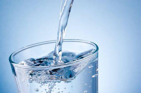 Verter agua en un vaso sobre un fondo azul. Foto de archivo