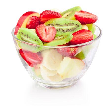 Ensalada de frutas frescas en un tazón de vidrio aislado sobre un fondo blanco.