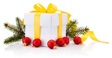 White gift box tied yellow ribbon bow, Christmas baubles and fir tree branch Isolated on a white background