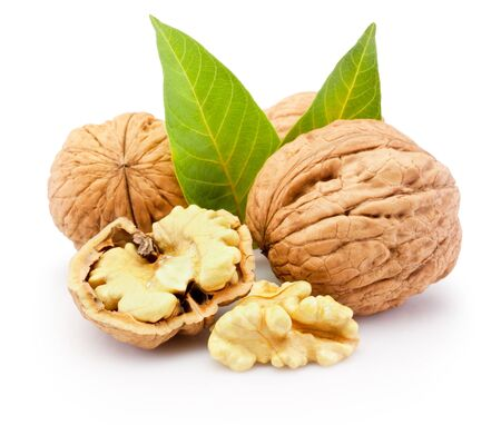 Kernel and whole walnuts with leaves isolated on a white background