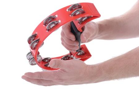 pandero: manos que se juegan pandereta musical rojo sobre fondo blanco Foto de archivo
