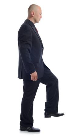 climbing stairs: Vista lateral del hombre en traje intensificando aislado en blanco