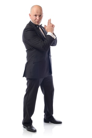 undercover agent: Man in tuxedo in a 007 james bond pose Stock Photo