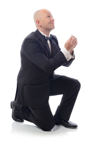 man in tuxedo down on bended knee proposing isolated on white photo