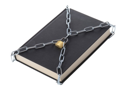 padlocked: concept of security a book padlocked with chains isolated on white