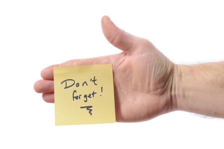 post it note with don't forget as a reminder note on hand isolated on white photo