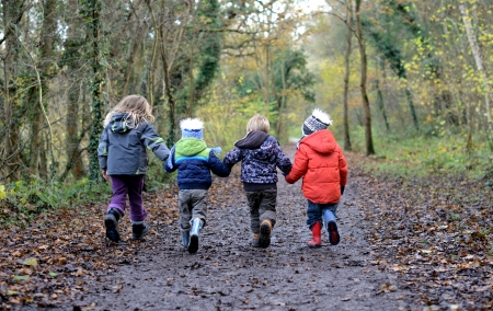 four children holding hands walking down a wooded path having fun