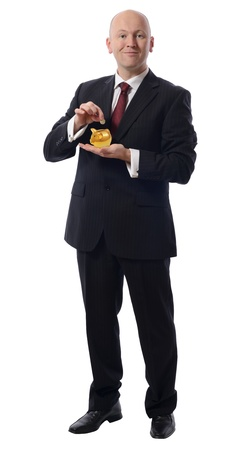coins shot in golden color: businessman dropping a pound into  a golden piggybank isolated on white