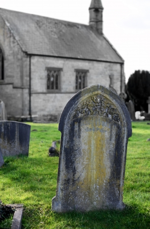 in loving memory: Aged old gravestone head in a peacefull churchyard