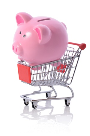trolly: Concept of savings on shopping, piggy bank in a shopping trolly isolated on white