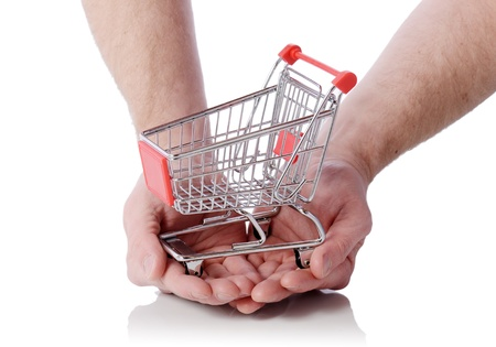 Hand holding shopping cart trolly isolated on white, concept of shopping at your finger tips photo