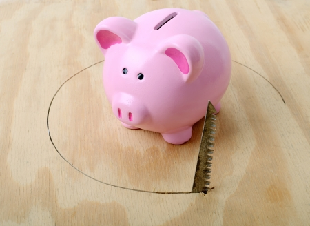 sawed: Concept of troulbled finances piggy bank with hole being sawed from under neath