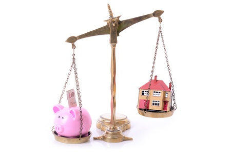 subprime mortgage crisis: concept of mortage and saving piggy bank and house on scales  Stock Photo