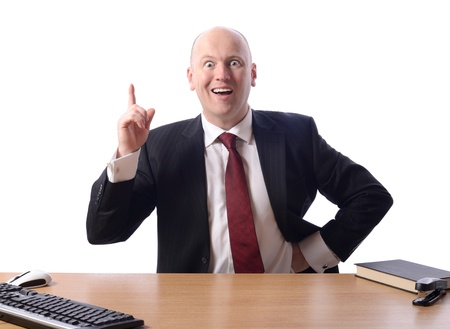 raised eyebrows: businessman sat at desk with a great idea or plan, isolated on white background
